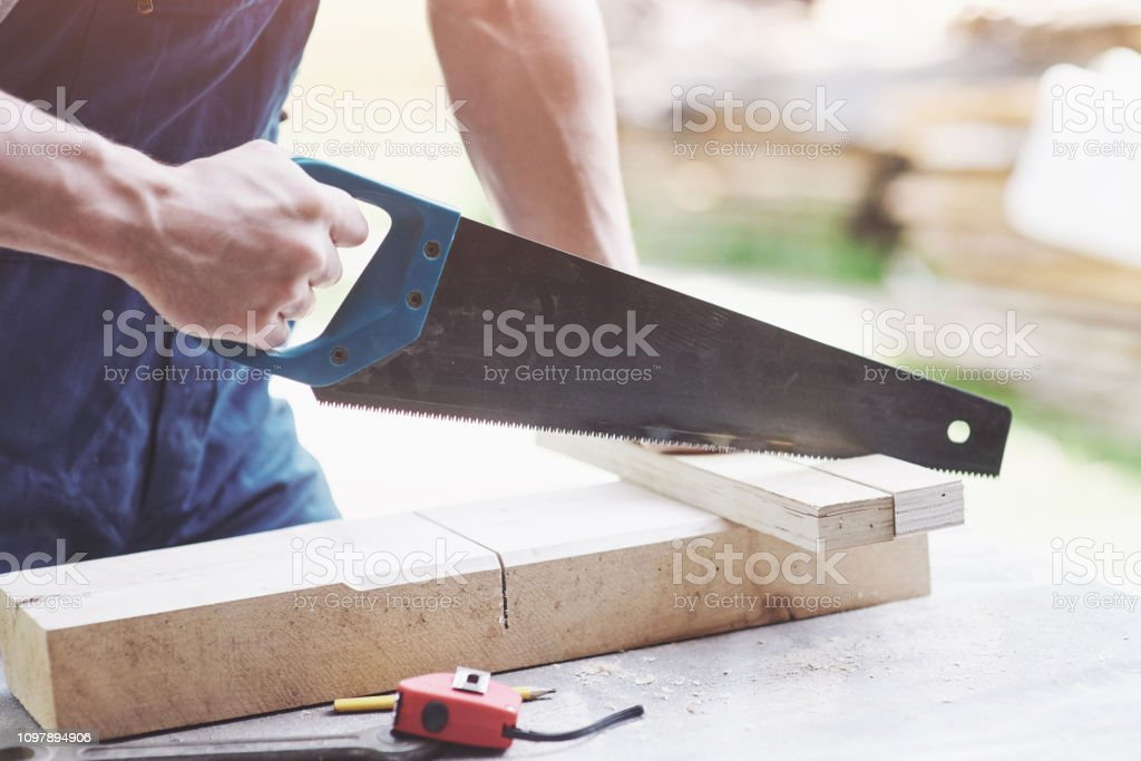 Beautiful strong hand joiner saws a wooden board