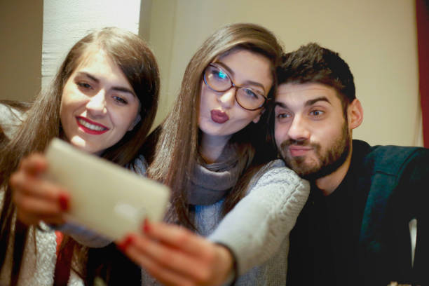 beautiful students make selfie in a cafe - brunette woman eyeglasses kiss man foto e immagini stock