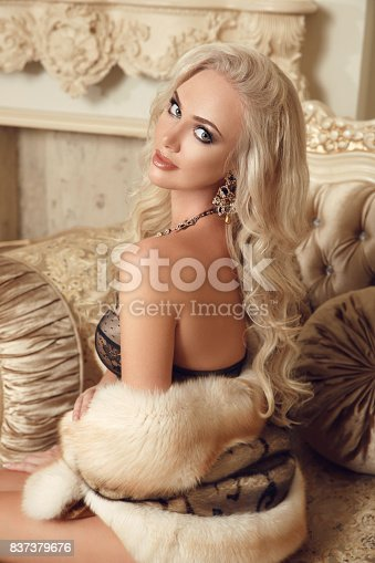 Beautiful stunning blond woman in sexy lingerie with fur sitting on royal sofa in luxury modern interior. Beauty glamour fashion style photo portrait.