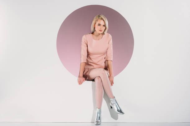 mooie stijlvolle blonde vrouw in jurk en glanzende schoenen in gat zitten en kijken naar camera op grijs - modieus stockfoto's en -beelden