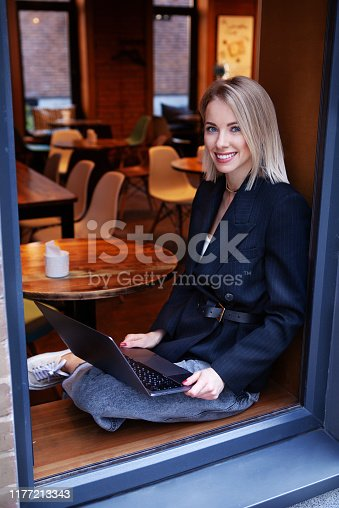 Beautiful stylish businesswoman freelancer or student sitting in cafe and working on laptop computer. Young happy woman looking at camera and smiling, online education
