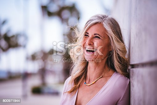 istock Beautiful stylish senior woman laughing leaning against wall outdoors 800971944