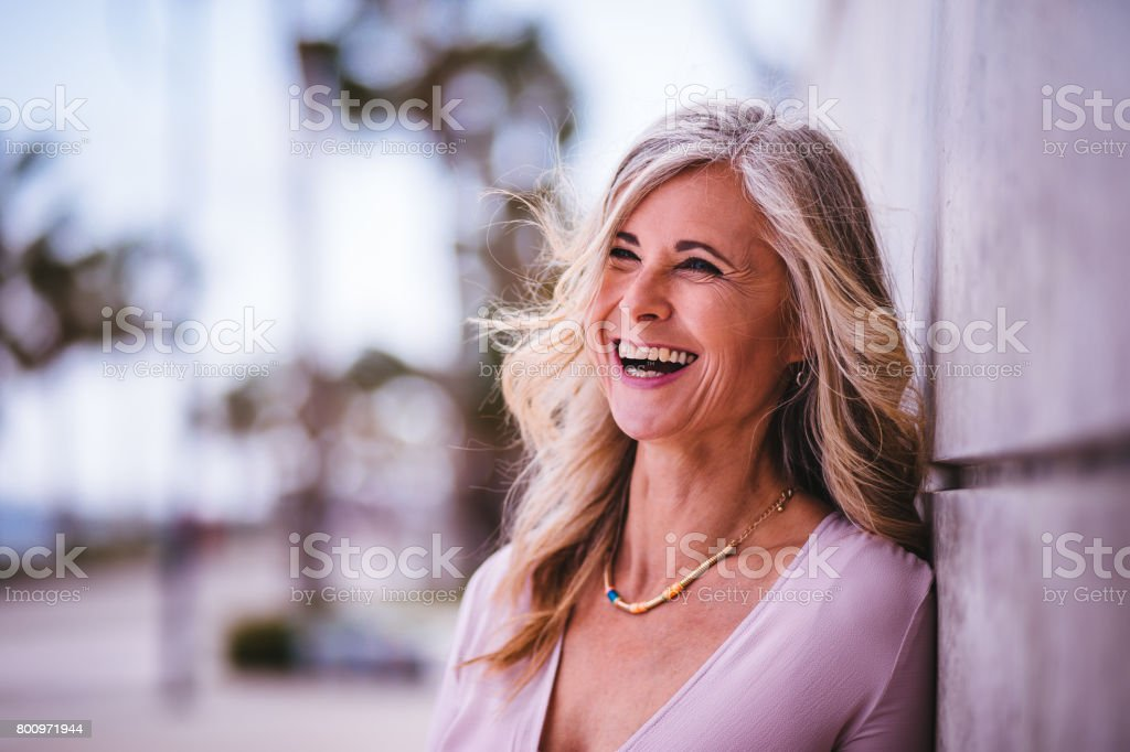 Beautiful stylish senior woman laughing leaning against wall outdoors stock photo