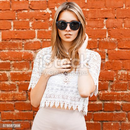 578791454istockphoto Beautiful stylish woman in a white vintage lace blouse, sunglasses 578587358