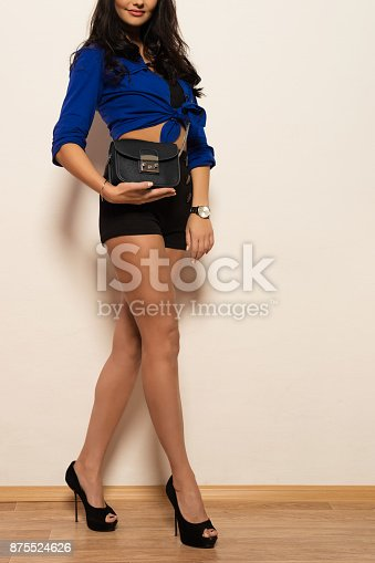 539468216 istock photo beautiful stylish young brunette woman in high heels holds a fashionable clutch in hands 875524626