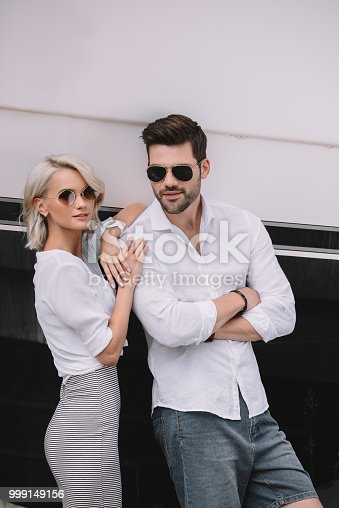 beautiful stylish young couple in sunglasses smiling at camera on yacht