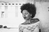 black white portrait of beautiful young cuban woman leaning on concrete wall
