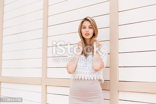 578791454istockphoto Beautiful stylish young woman in a vintage lace blouse with an ornament in a beige skirt with a brilliant necklace posing near a wooden wall on a summer day. Charming girl. 1129141732