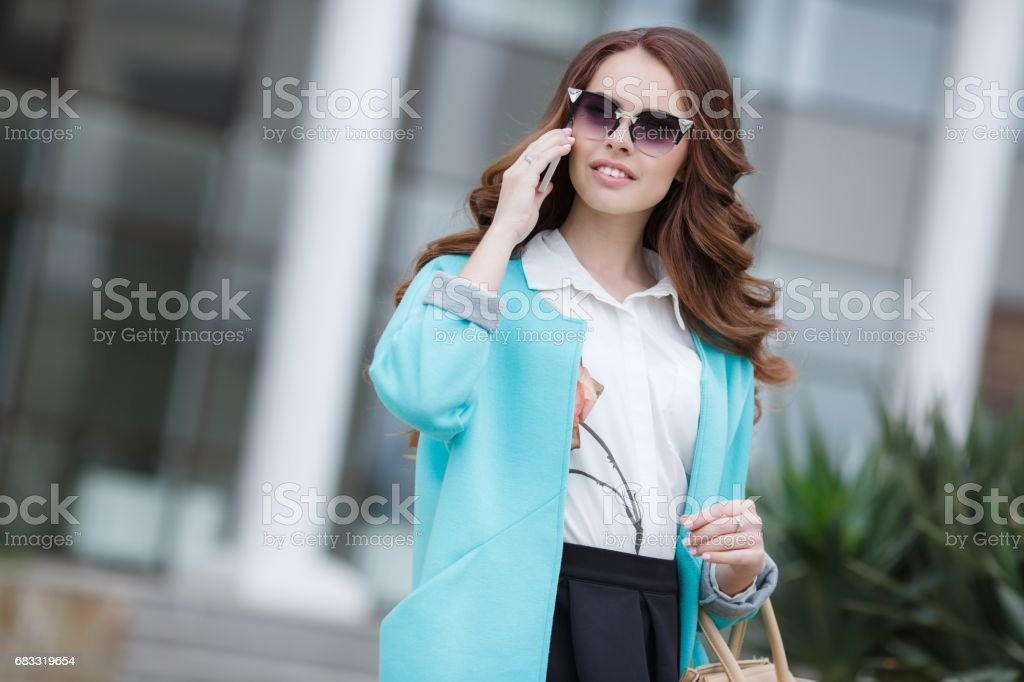 Beautiful stylish young woman with a beige handbag royalty-free stock photo