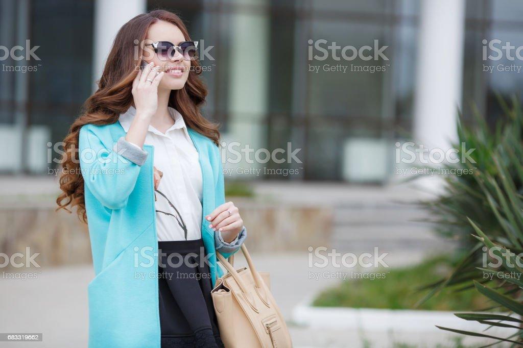 Beautiful stylish young woman with a beige handbag zbiór zdjęć royalty-free
