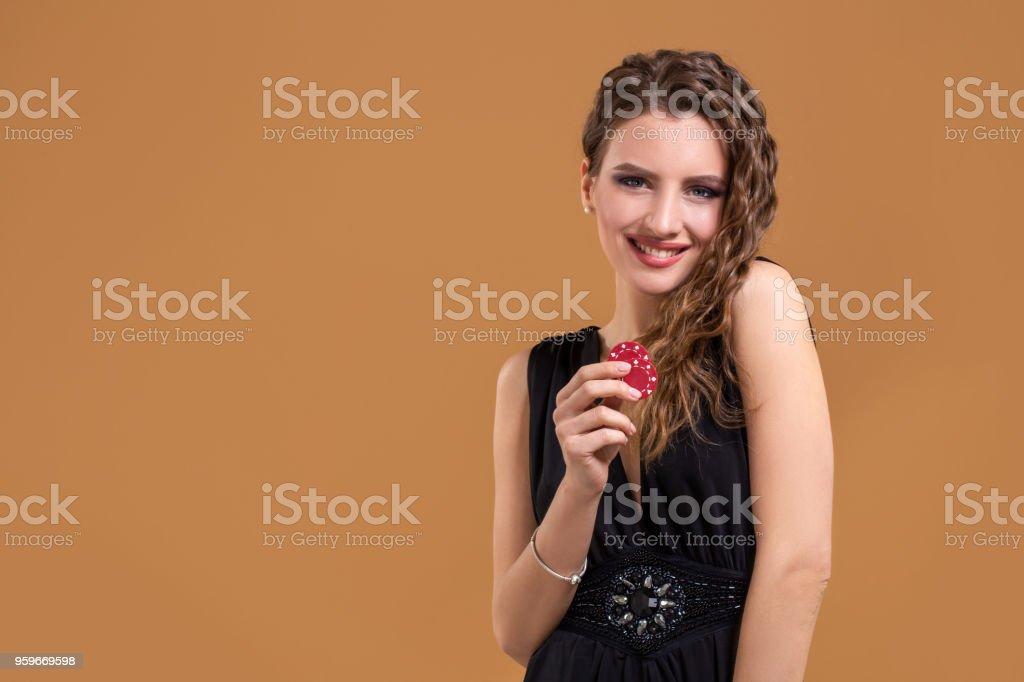 Hermosa mujer joven elegante con poker chips en la mano, sobre fondo beige - Foto de stock de Adulto libre de derechos