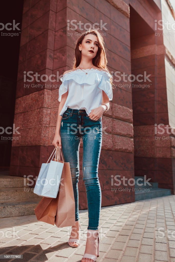bac71f01 Beautiful stylish young woman with shopping bags walking on city street.  Slim model wearing closing