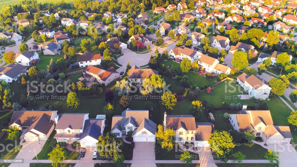 Beautiful suburban neighborhoods, nice homes, Summertime aerial view at dawn.