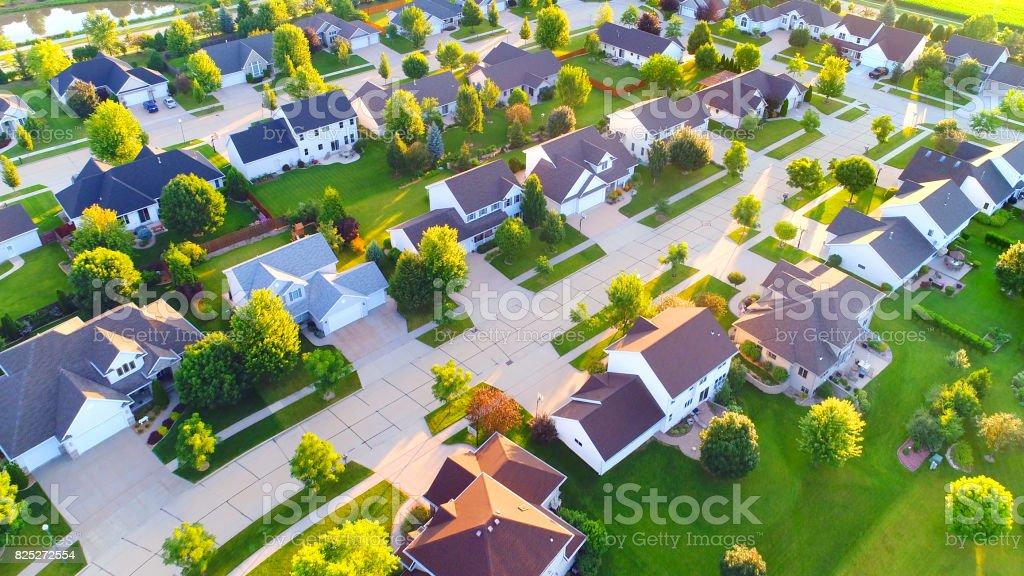Beautiful suburban neighborhoods, nice homes, Summertime aerial view at dawn.