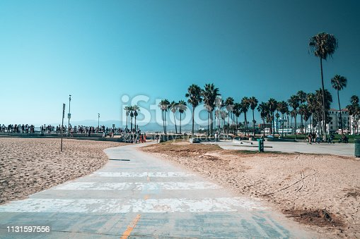 Beautiful summer day at the Venice beach district in LA with people skating, chilling under the palms and shopping. Summer vibes and spirit in LA.