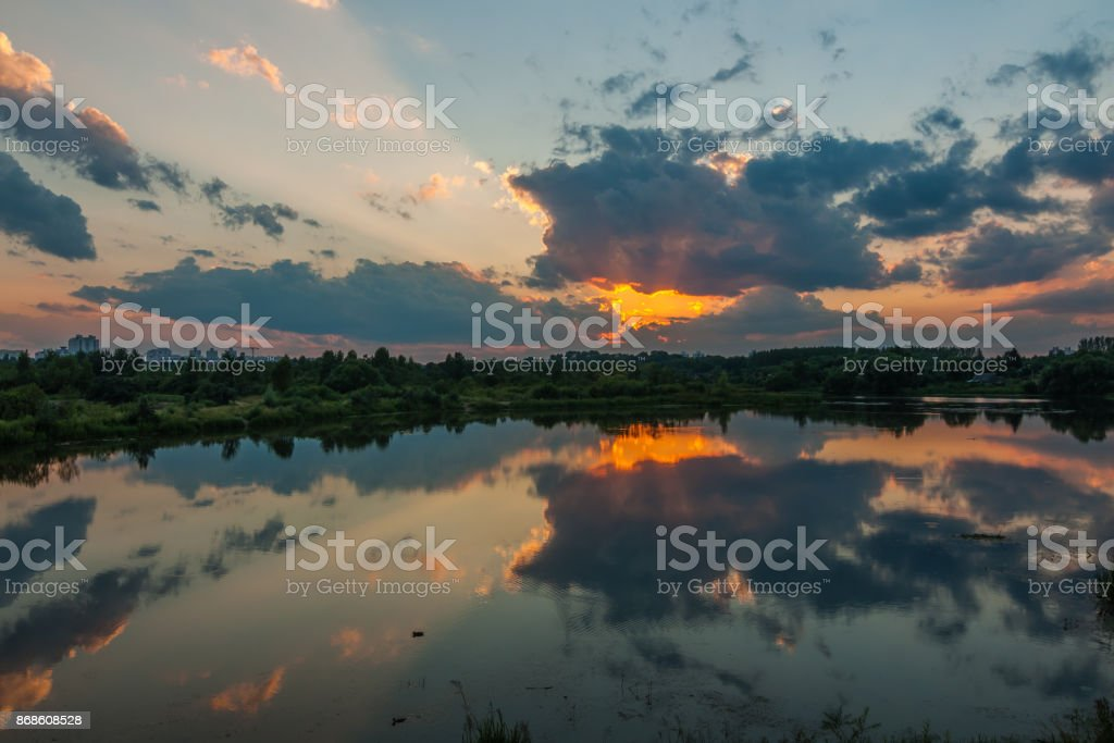 Uma noite linda de verão. O dramático pôr do sol reflete na água lisa do rio ou lago na periferia urbana - foto de acervo