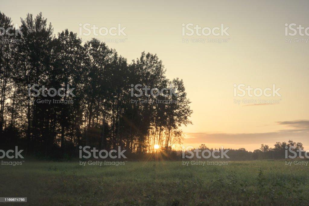 Vackert sommar landskap i Sverige med solen stiger i horisonten - Royaltyfri Dramatisk himmel Bildbanksbilder