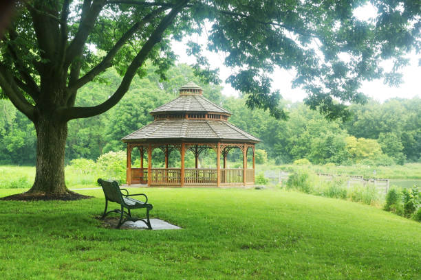Beautiful summer rainy day nature background. Summer landscape in a city park with a bench on a foreground and wooden gazebo on a background during warm rainy day. pavilion stock pictures, royalty-free photos & images