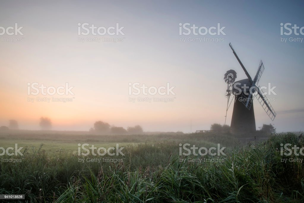 Beautiful Summer sunrise landscape over Thurne Drainage Mill in Norfolk Broads England stock photo