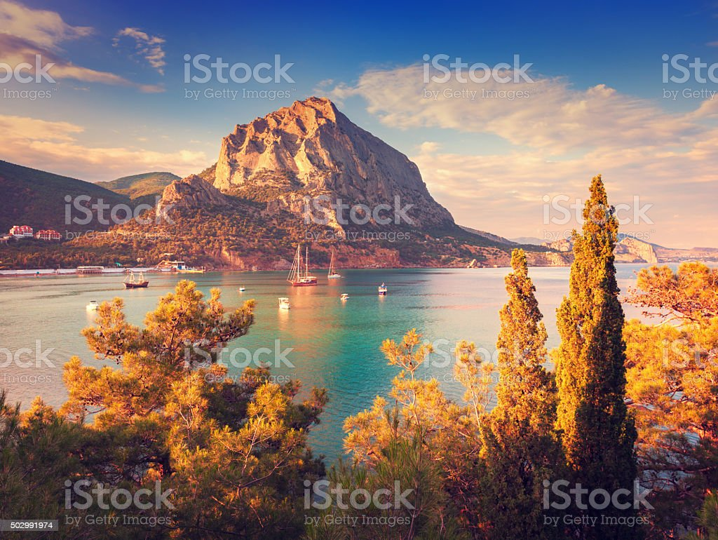 Beautiful summer sunset at the sea with mountains and trees stock photo