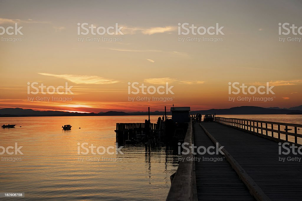 Beautiful Summer sunset over the water by a pier stock photo