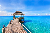 Beautiful tropical summer beach landscape, luxurious hotel wooden pier with transparent turquoise sea water
