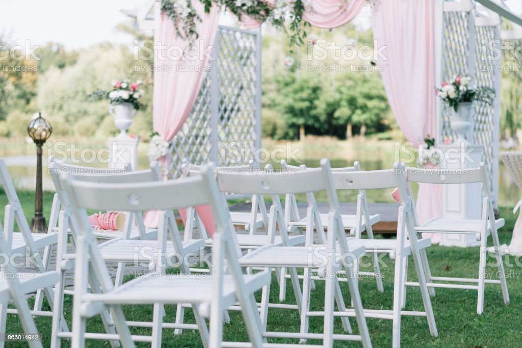 Beautiful Summer Wedding Ceremony Outdoors. Decorated Chairs Stand On The  Grass. Wedding Arch Made