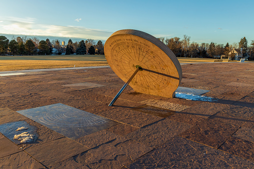 Beautiful sundial in the Cranmer Park, Denver, Colorado, with trees and Denver cityscape on background