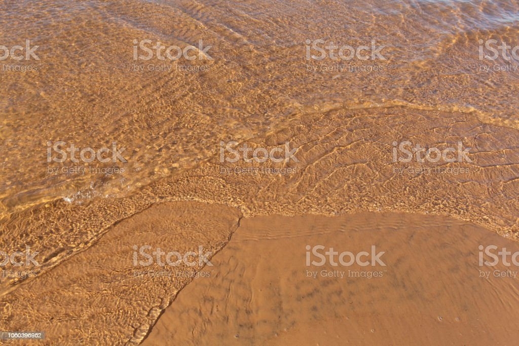 Beautiful sunlit small waves of shallow clear water on the smooth sand stock photo