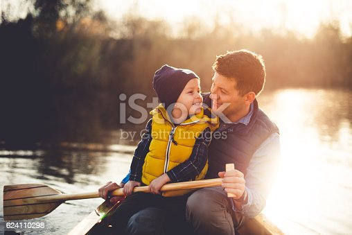 Dad and son enjoying canoe ride on a beautiful sunny day,