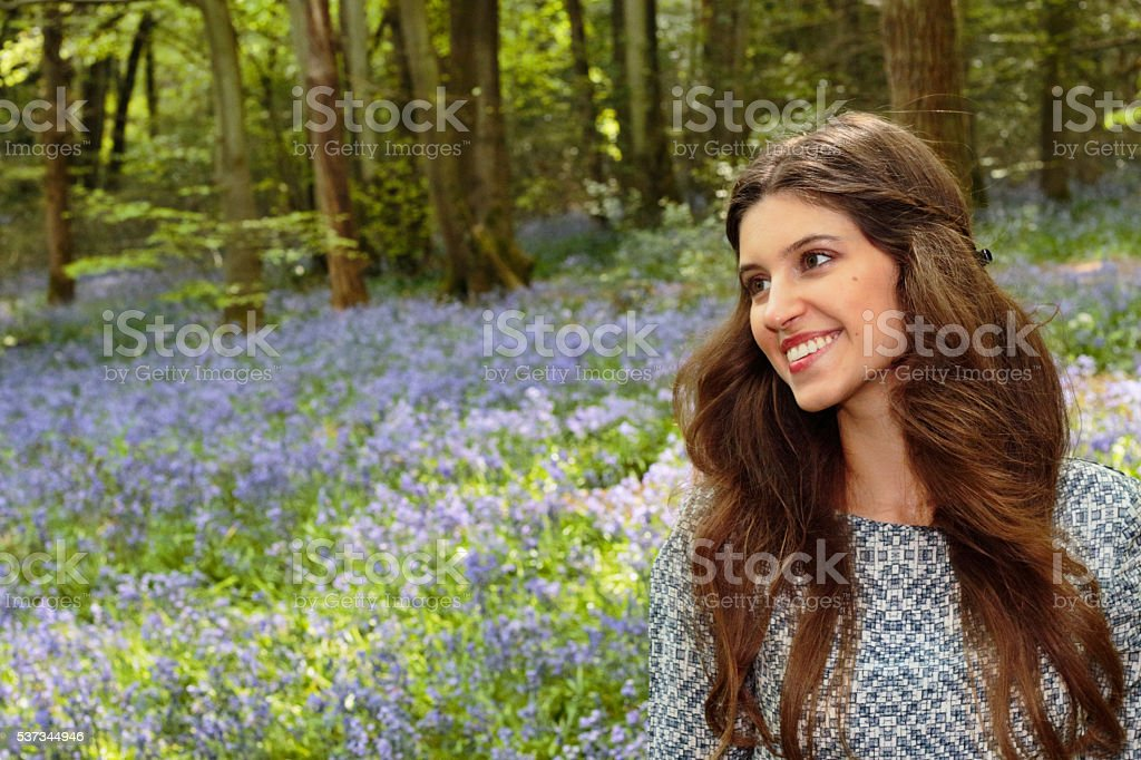 Smiling blue belle Russian outdoor girl in bluebell wood Surrey stock photo
