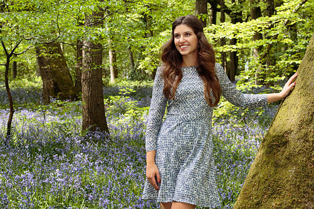 blue belle russian outdoor girl standing against beech tree trunk - whiteway english outdoor girl stock photos and pictures