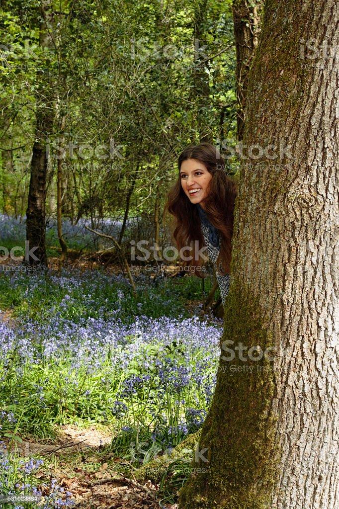 Peek-a-boo blue belle Russian outdoor girl behind beech tree stock photo
