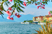 Amazing sunny summer view of Bellagio town at lake Como in Italy with blooming nerium oleander flowers, ships and boats