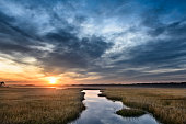 Marsh lands and ocean inlet with clouds reflecting in water at Chincoteague Island, Virginia.