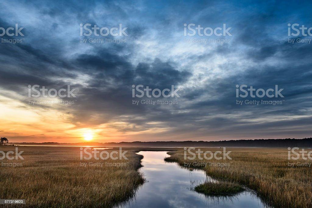 Beautiful Sunrise Along Coastal Inlet with Dramatic Clouds stock photo