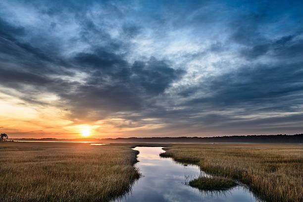 beautiful sunrise along coastal inlet with dramatic clouds - mokradło zdjęcia i obrazy z banku zdjęć