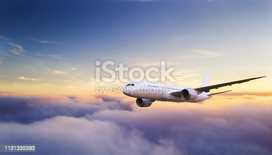 Huge two-storey passengers commercial airplane flying above clouds in sunset light. Concept of fast travel, holidays and business.