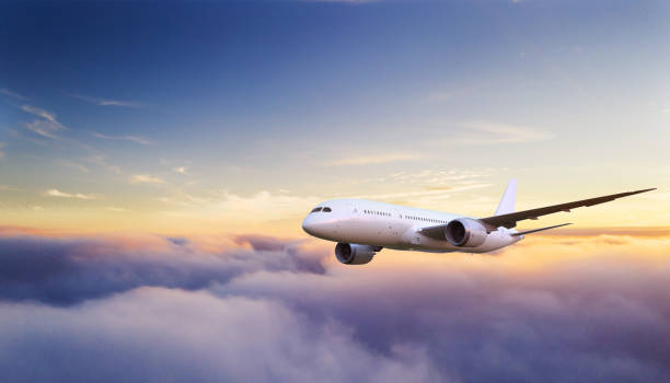 Beautiful sunrise cloudy sky from aerial view Huge two-storey passengers commercial airplane flying above clouds in sunset light. Concept of fast travel, holidays and business. flying stock pictures, royalty-free photos & images