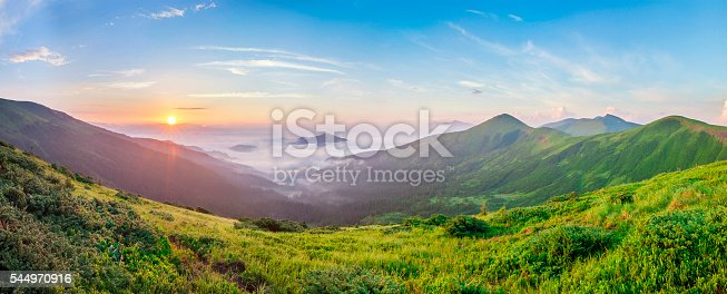 istock Beautiful sunrise in mountains with white fog below panorama 544970916