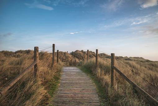 Beautiful sunrise landscape image of sand dunes system over beach with wooden boardwalk