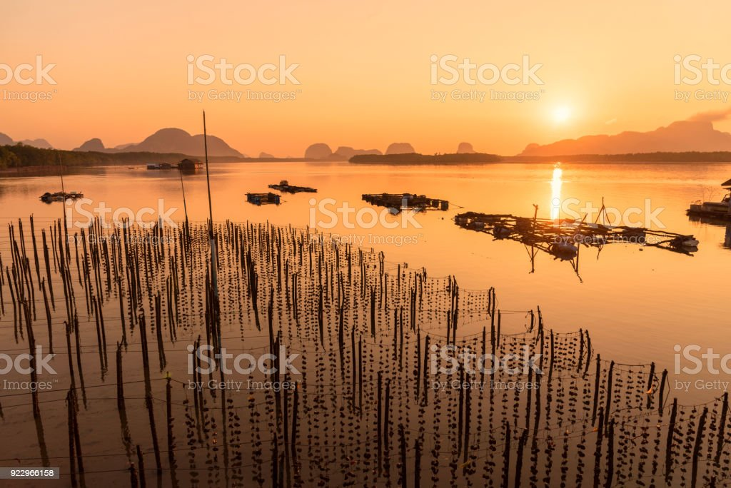 Beautiful sunrise landscape view of fisherman village and wooden boat in early morming at Samchong-tai fishing village in Phang-Nga,Thailand stock photo