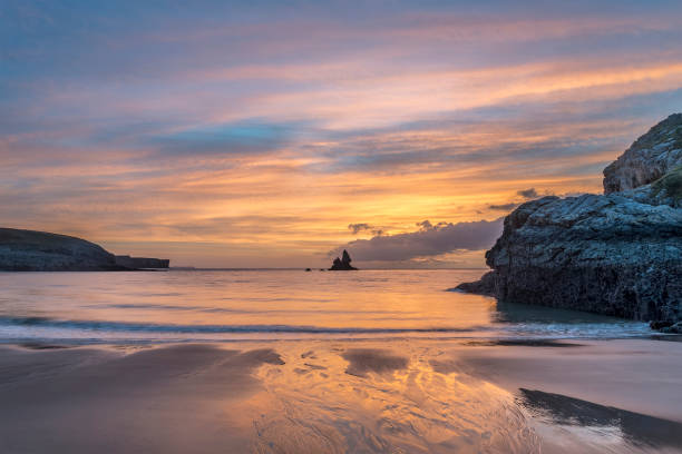 Beautiful sunrise landsdcape of idyllic Broadhaven Bay beach on Pembrokeshire Coast in Wales Stunning sunrise landsdcape of idyllic Broadhaven Bay beach on Pembrokeshire Coast in Wales south wales stock pictures, royalty-free photos & images
