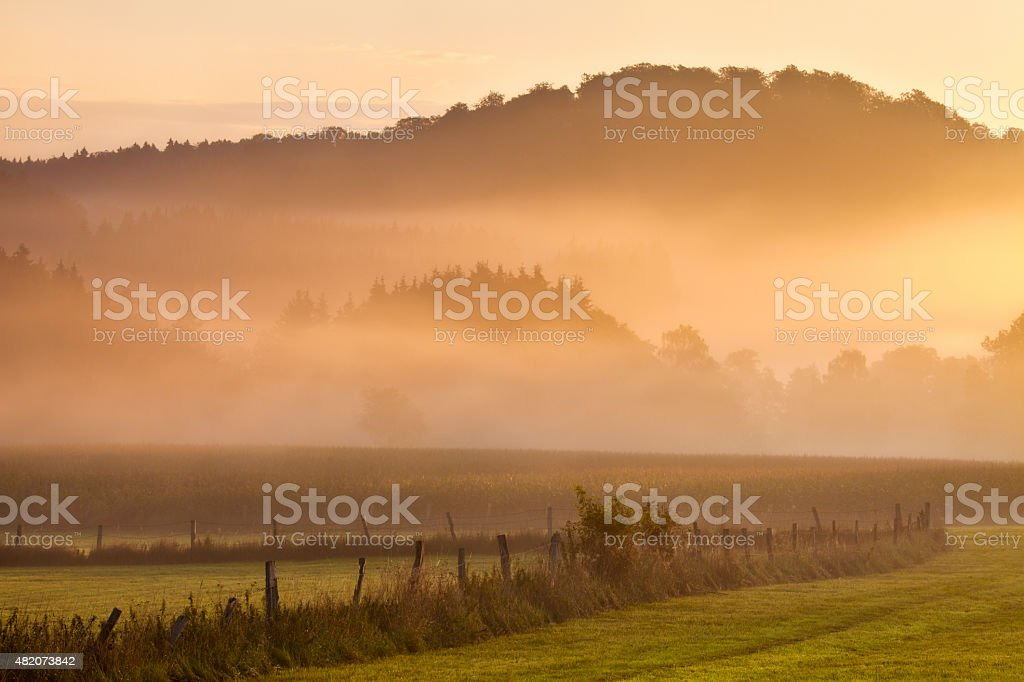 Beautiful sunrise, misty morning in idyllic rural Sauerland, Germany, countryside stock photo