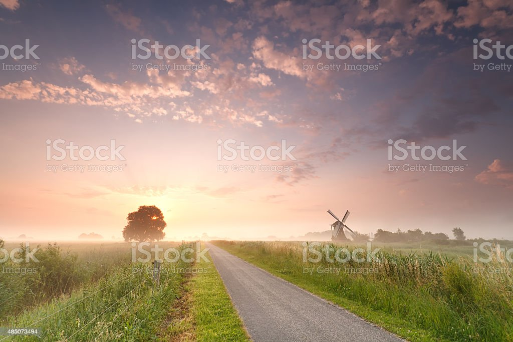 beautiful sunrise on Dutch farmland with windmill stock photo