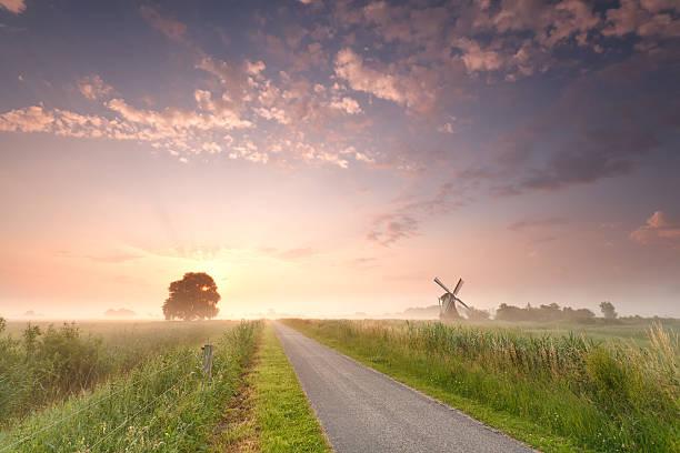 beautiful sunrise on Dutch farmland with windmill stock photo