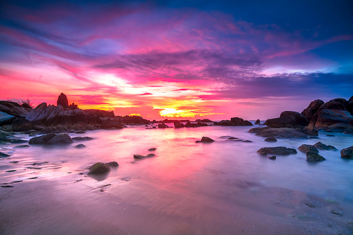 Beautiful sunrise on the beach below the waves lapping at the shore of the soft great to welcome the peaceful new day