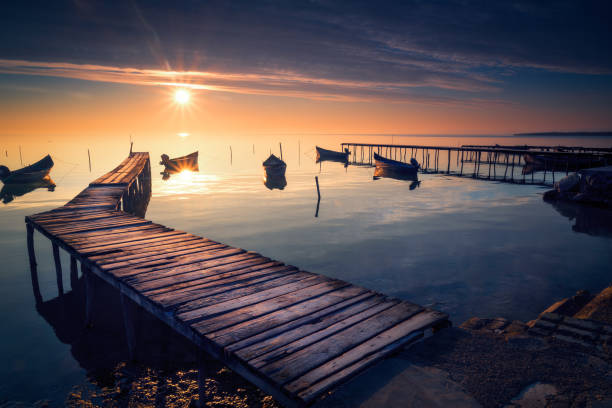 Beautiful sunrise or sunset on a calm lake with several fishing boats  and wooden pontoons stock photo
