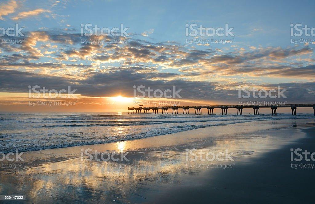 Beautiful sunrise over ocean horizon and pier. stock photo