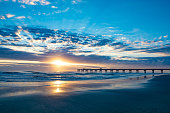 Sun rising over horizon and pier, beach illuminated with sunlight, beautiful sky reflected on the beach. Jacksonville Florida, USA.